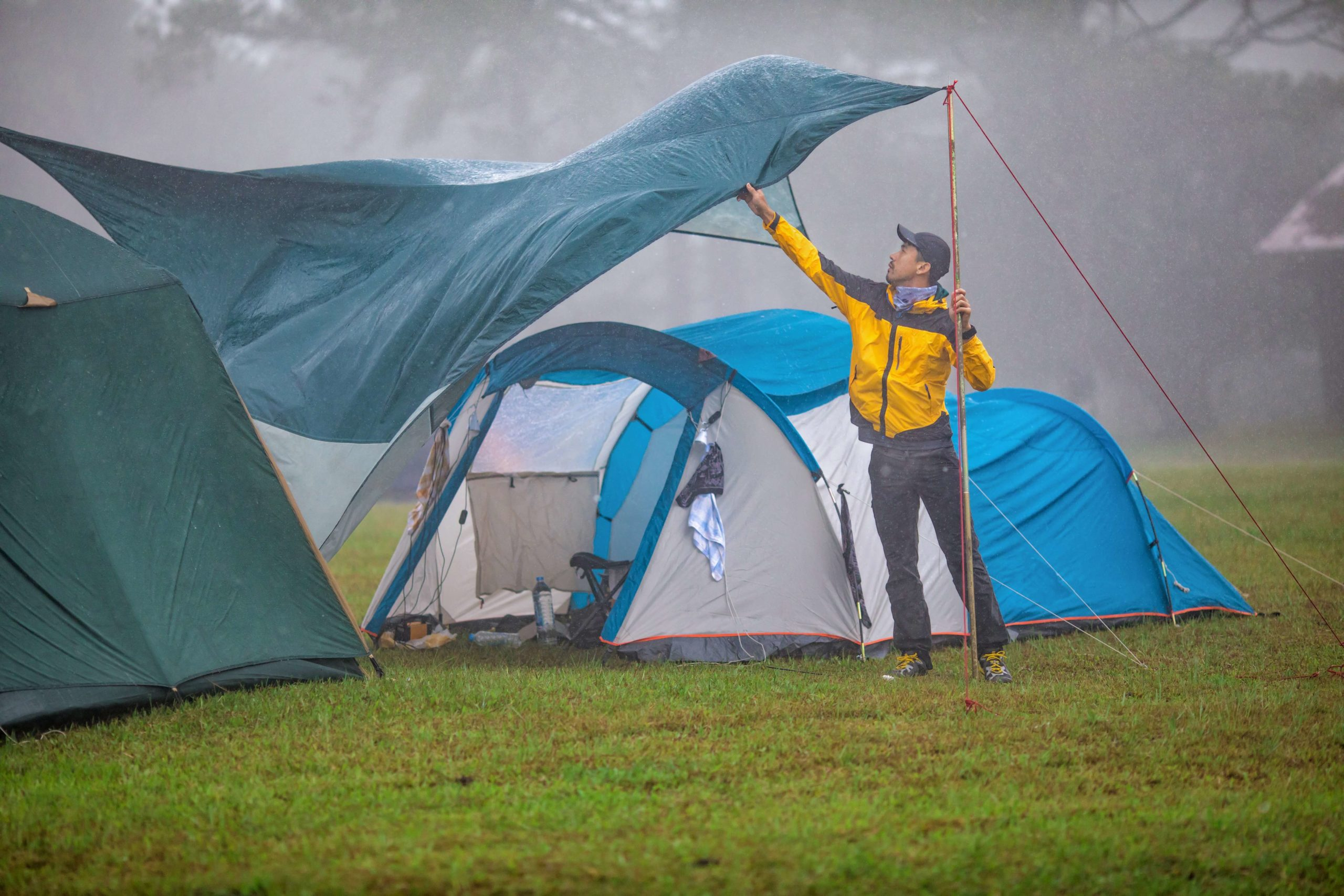 Man covering tents with a tarp during a rainstorm; a conceptual image about preparation, a key reason for following pcb design for testability guidelines